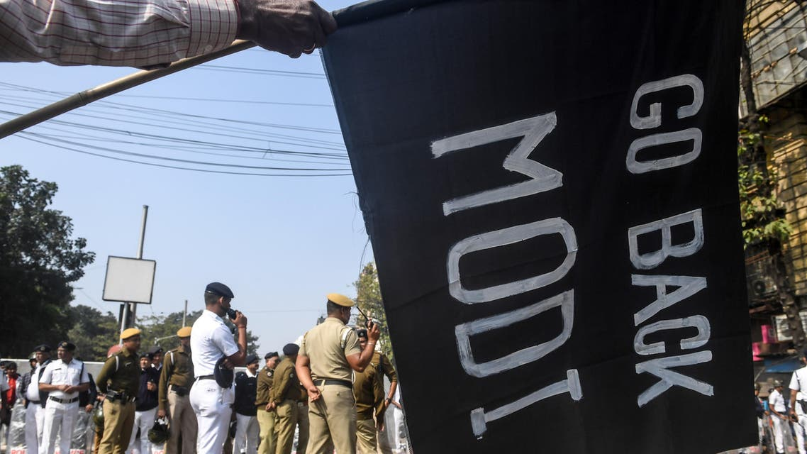 A demonstrator holds a flag on which is written 'Go Back Modi' to protest against Indian Prime Minister Narendra Modi as police personnel stands guard, during a demonstration in Kolkata on January 12, 2020. (AFP)