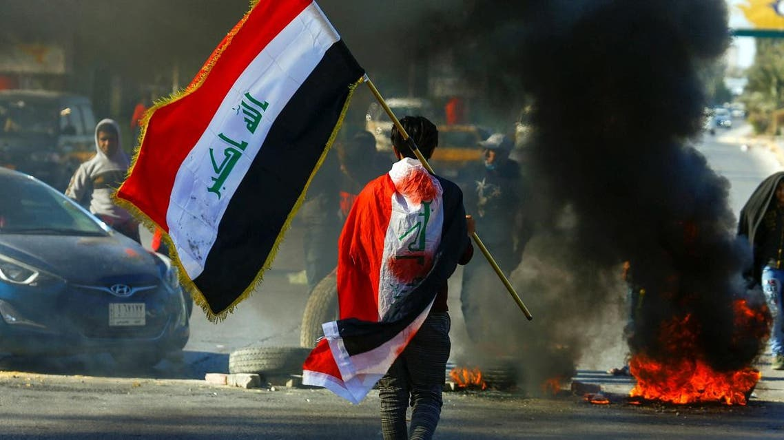 A demonstrator carries an Iraqi flag as he walks near burning tires, during ongoing anti-government protests in Najaf, Iraq January 12, 2020. (Reuters)