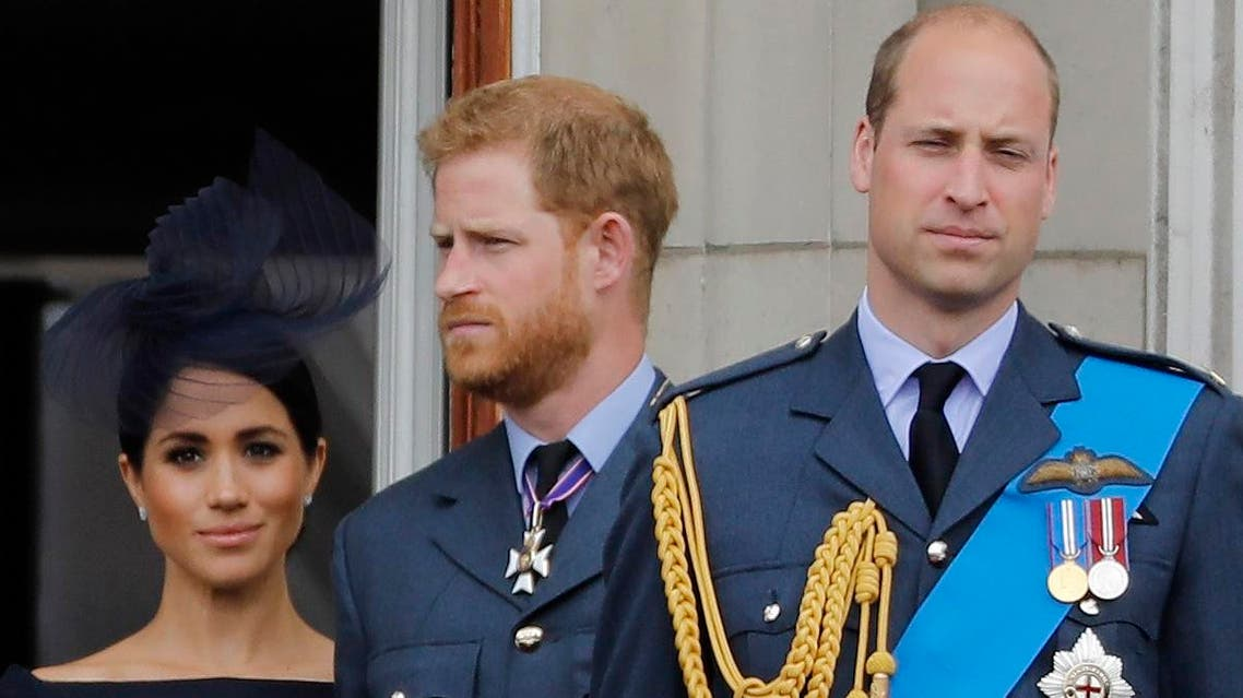 (L-R) Britain's Meghan, Duchess of Sussex, Britain's Prince Harry, Duke of Sussex, and Britain's Prince William, Duke of Cambridge, stand on the balcony of Buckingham Palace to watch a military fly-past to mark the centenary of the Royal Air Force (RAF). (AFP)