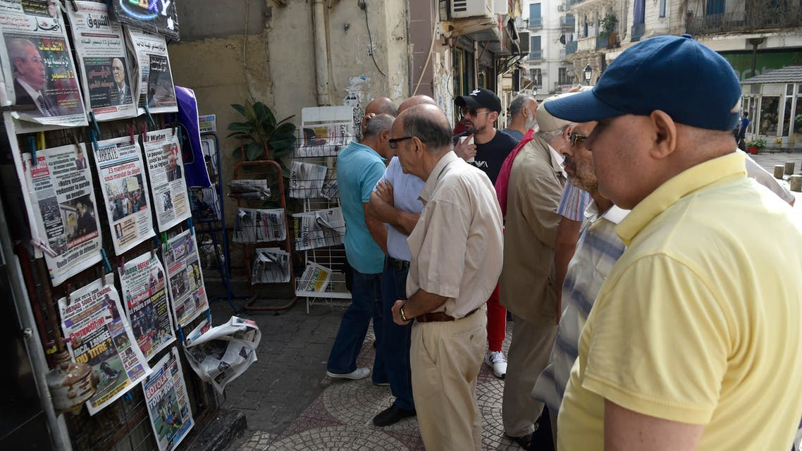 People view the covers of national and foreign newspapers, with the announced Algerian presidential election date dominating headlines, at a stand in Algeria's capital Algiers on September 16, 2019. Algeria is to hold presidential elections on December 12, five months into a political vacuum since longtime leader Abdelaziz Bouteflika resigned in the face of mass protests, his interim successor announced on September 15. The announcement comes after army chief General Ahmed Gaid Salah, seen as Algeria's strongman since the fall of the ailing Bouteflika, insisted that polls be held by the end of 2019, despite ongoing protests demanding the creation of new institutions ahead of any elections.