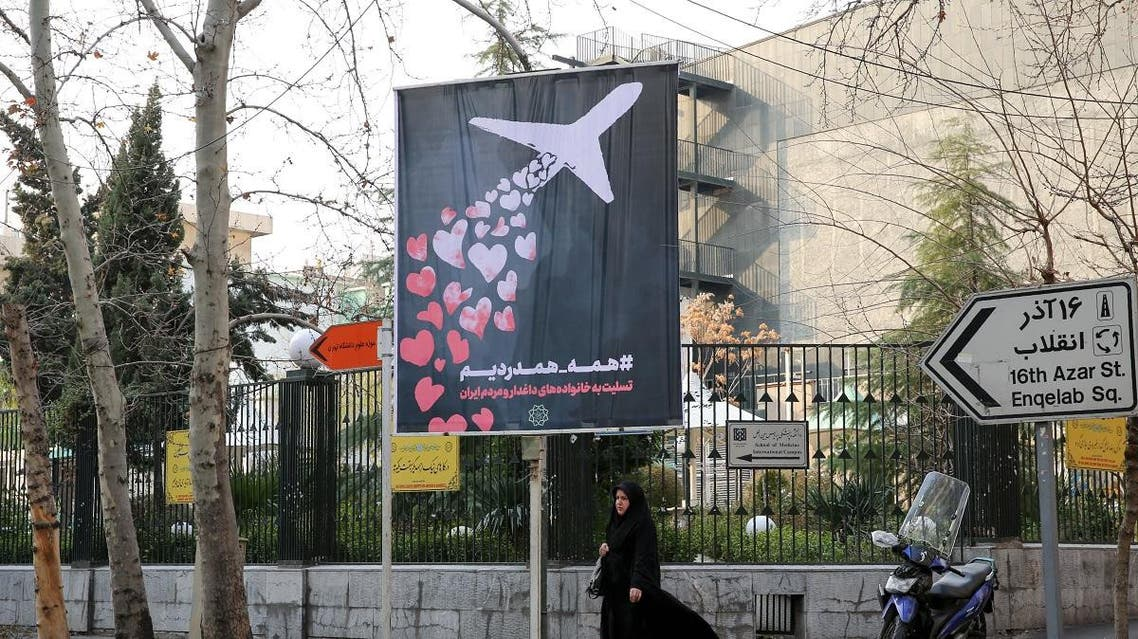 An Iranian woman walks beneath a poster honouring the victims of a Ukrainian passenger jet accidentally shot down in the capital last week, in front of the Amirkabir University in the capital Tehran, on January 13, 2020. (AFP)