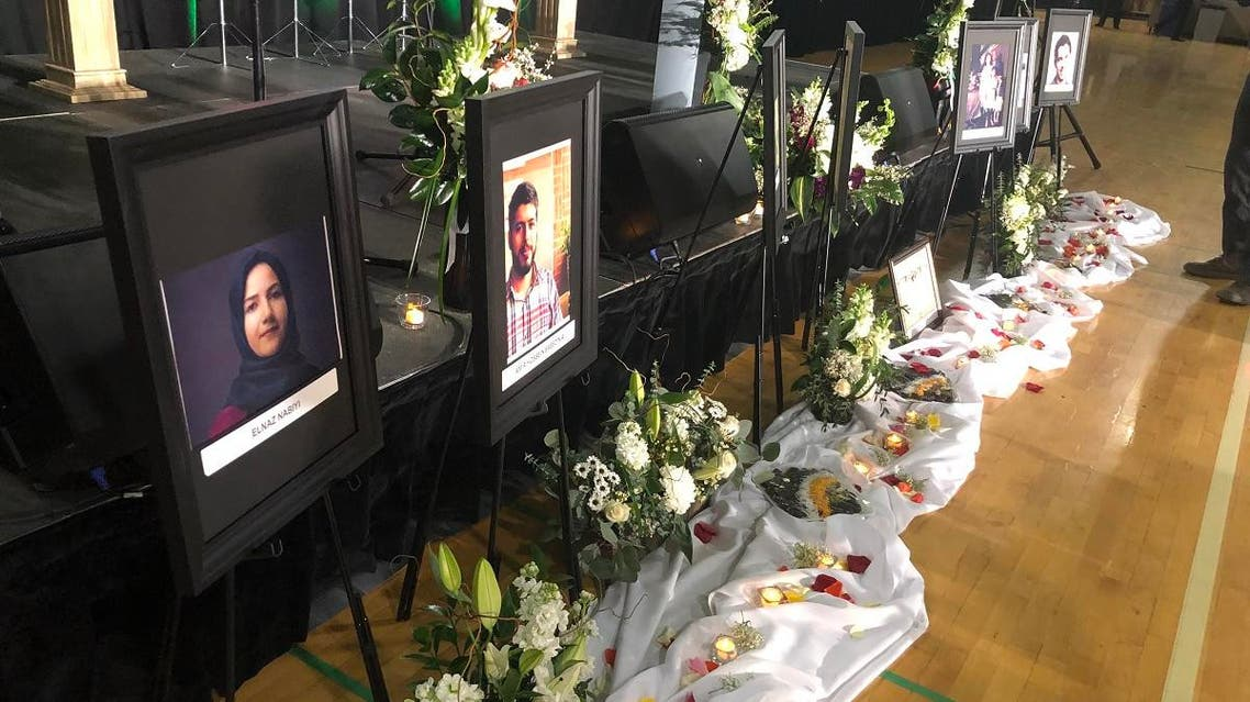 Photos of the victims are seen in front of the stage before the start of a memorial service for the Ukrainian Airlines flight PS752 who crashed in Iran at the Saville Community Sports Centre in Edmonton, Canada, on January 12, 2020. (AFP)