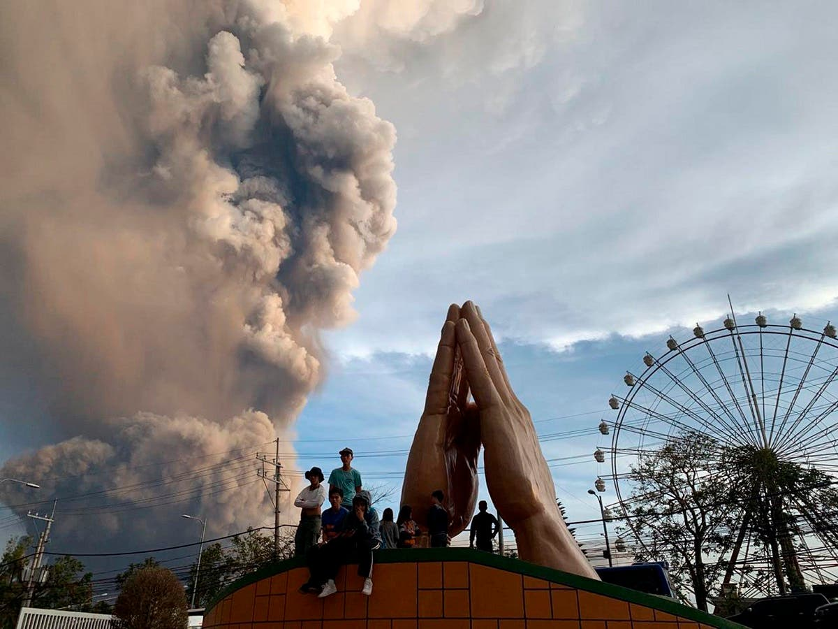 People watch as the Taal volcano spews ash and smoke during an eruption in Tagaytay, Cavite province south of Manila, Philippines on Sunday. Jan. 12, 2020. (Photo: AP)