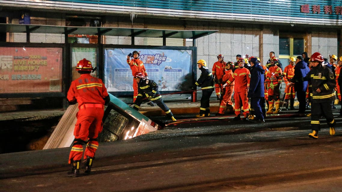 This photo taken on January 13, 2020 shows Chinese rescuers watching as a car is lifted out after a road collapse in Xining in China's northwestern Qinghai province. An enormous sinkhole swallowed passers-by and a public bus in northwest China, reported state media on January 14, injuring fifteen people while another ten are still missing.