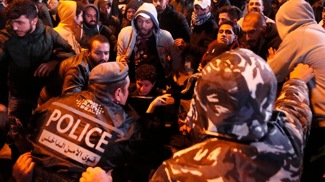 Lebanese policemen try to remove anti-government protesters to reopen a main road that was closed during ongoing protests against the ruling elite of corruption and financial crisis, in Beirut, Lebanon, Monday, Jan. 13, 2020. (AP)