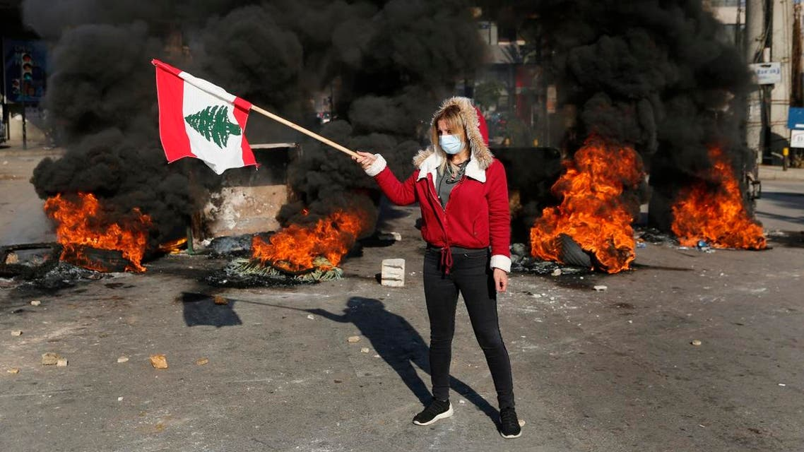An anti-government protester waves a national flag during ongoing protests after weeks of calm in Beirut, Jan. 14, 2020. (File Photo: AP)