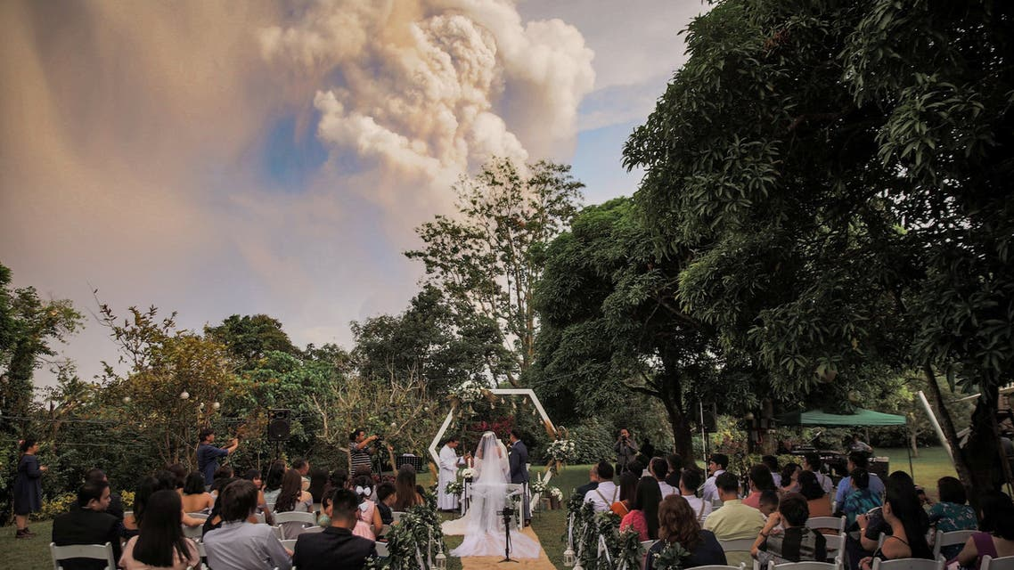 General view of a wedding ceremony as Taal Volcano sends out a column of ash in the background, in Alfonso, Cavite, Philippines January 12, 2020, in this image obtained from a social media video. Jay-Ar Fortaleza via REUTERS ATTENTION EDITORS - THIS IMAGE HAS BEEN SUPPLIED BY A THIRD PARTY. MANDATORY CREDIT. NO RESALES. NO ARCHIVES.