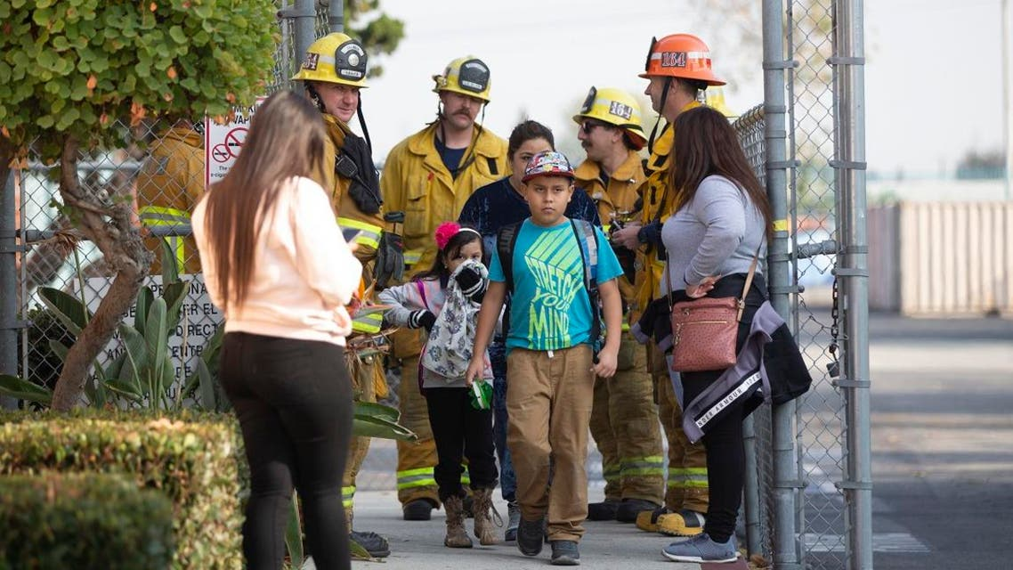 Children evacuate the Park Avenue Elementary school in Cudahy, Calif., after an aircraft dumped fuel that fell onto the elementary school playground. (Photo: AP)