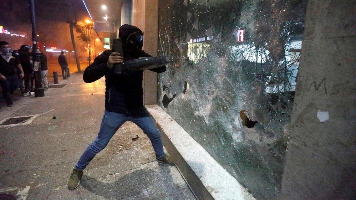 Protesters smash the window of a bank as demonstrations against the government continue in Beirut, Lebanon. (Reuters)