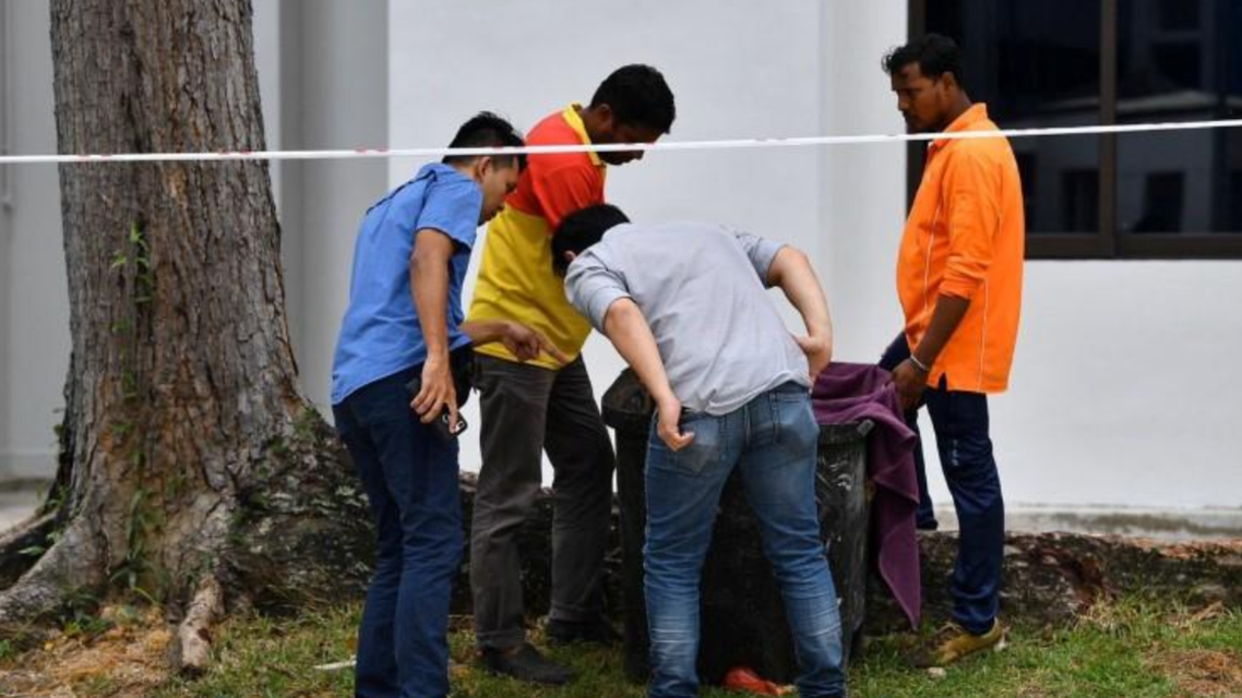 Police officers and cleaners inspect the contents of a bin at a rubbish chute, after a baby was found alive among rubbish in a bin at a public housing estate in Singapore, January 7, 2020. (Reuters)