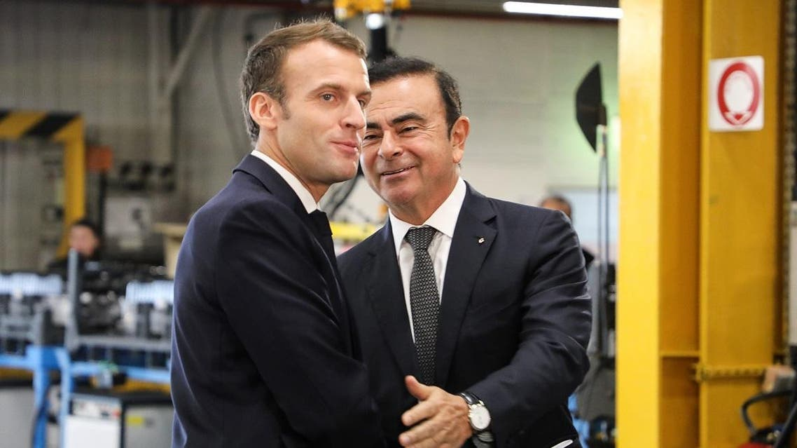French President Emmanuel Macron (L) shakes hands with Chairman and CEO of Renault-Nissan-Mitsubishi Carlos Ghosn (R) during a visit of the Renault factory, in Maubeuge, northern France, on November 8, 2018. (AFP)