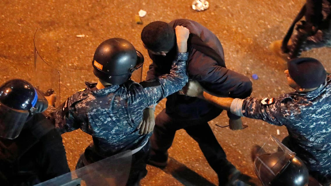 Riot police arrest an anti-government protester who was protesting outside a police headquarters demanding the release of those taken into custody the night before. (AP)