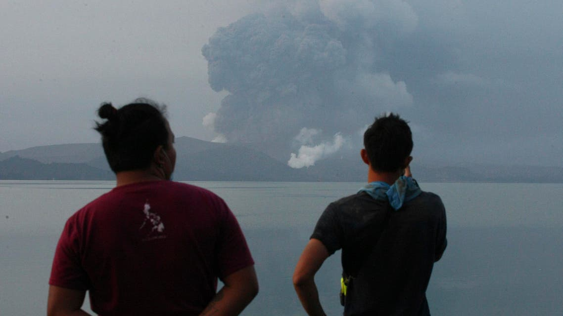 Residents watch Taal volcano spew ash from a look out in Talisay, Batangas province, southern Philippines on Monday, Jan. 13, 2020. (AP)