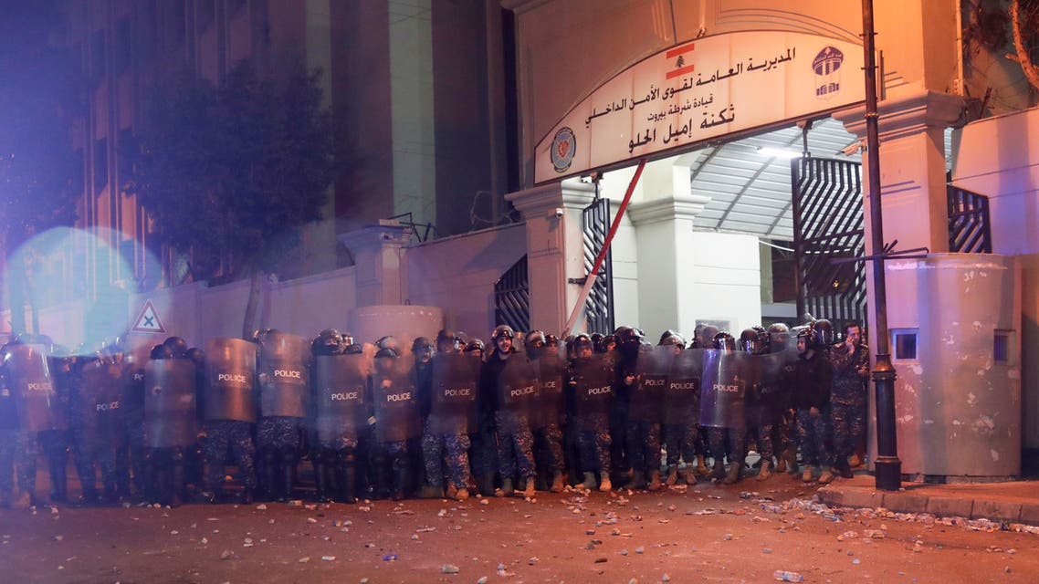 Riot police gather outside barracks during clashes with Lebanese anti-government protesters, following a gathering to demand the release of detainees who were arrested overnight, in the capital Beirut on January 15, 2020. Public anger against cash-strapped banks has boiled over in crisis-hit Lebanon, where demonstrators armed with metal rods, fire extinguishers and rocks attacked branches overnight in protest at controls that have trapped the savings of ordinary depositors. Police said 59 people were detained, in one of the largest waves of arrests since Lebanon's anti-government protests began on October 17 demanding sweeping reforms.