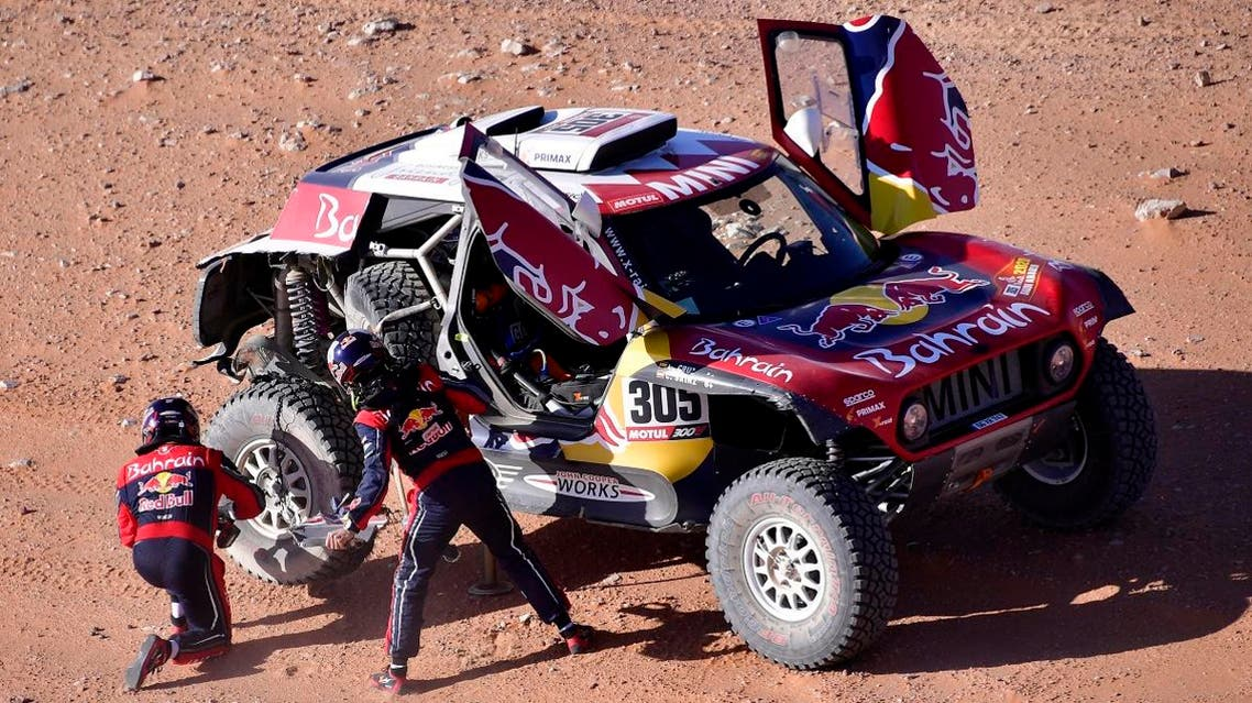 Mini's Spanish drivers Carlos Sainz of Spain and co-driver Lucas Cruz of Spain repairs their car after a flat tire during the 2020 Rally Dakar Stage 9 of the Dakar 2020 between Wadi Al Dawasir and Haradh, Saudi Arabia. (Reuters)