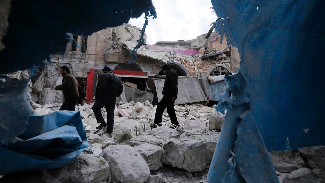 People walk past destruction by the government airstrikes in the town of Ariha, in Idlib province, Syria, on January 15, 2020. (AP)