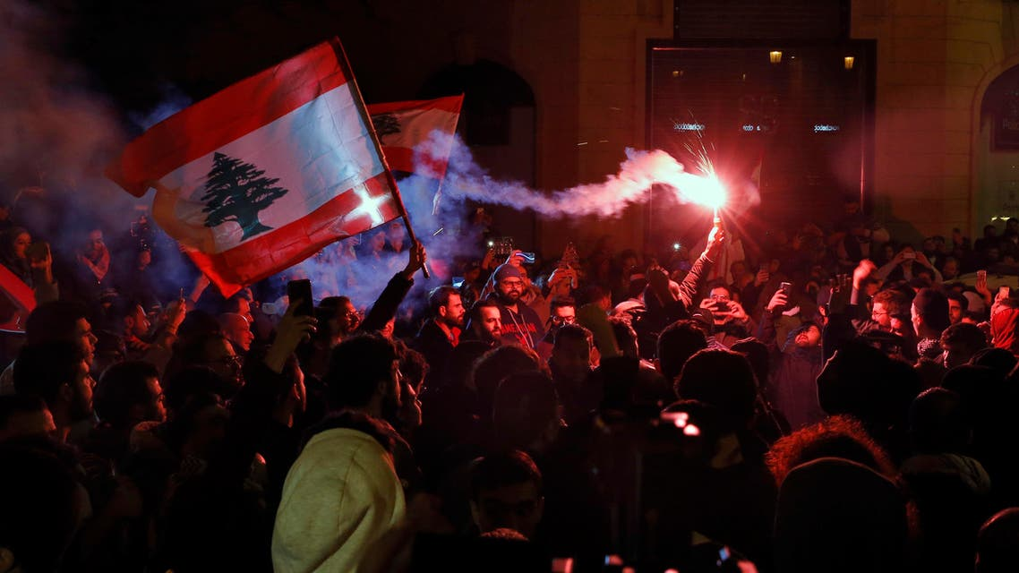 Anti-government demonstrators hold flares and Lebanese flags, during a protest on a road leading to the parliament building in Beirut, Lebanon, Thursday, Jan. 16, 2020. (AP)