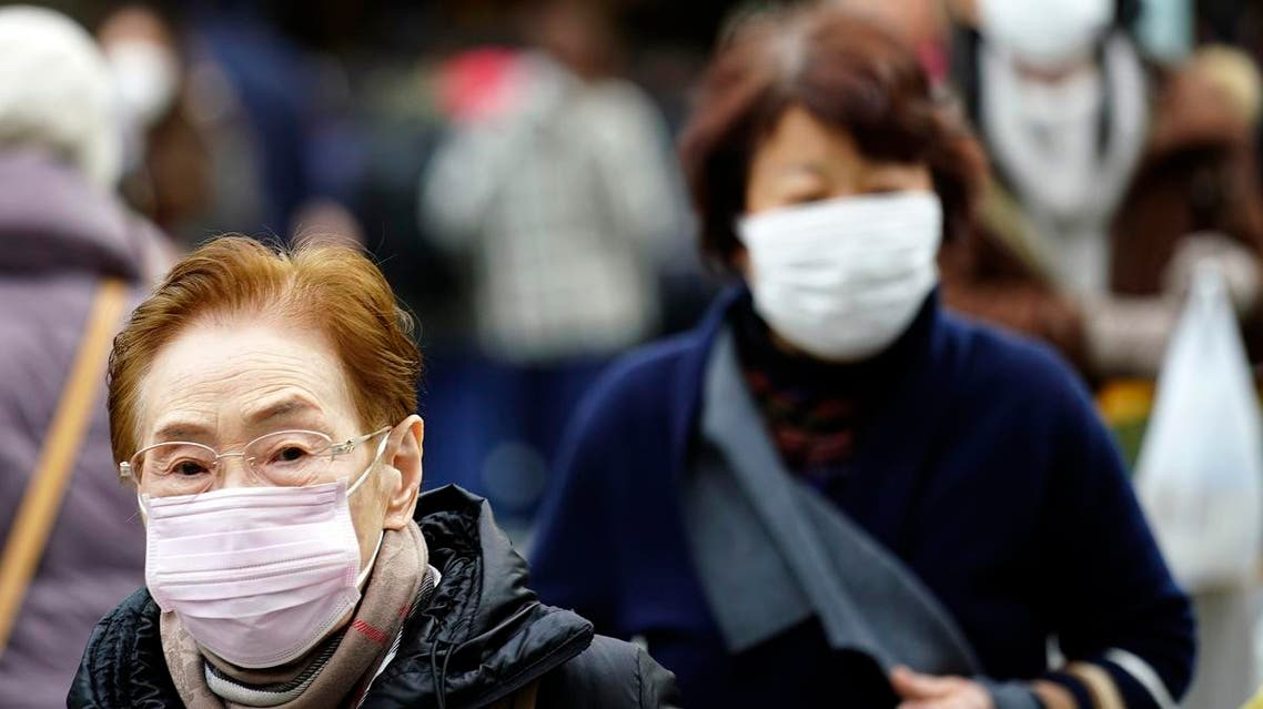 Pedestrians wear protective masks as they walk through a shopping district in Tokyo on January 16, 2020. (AP)