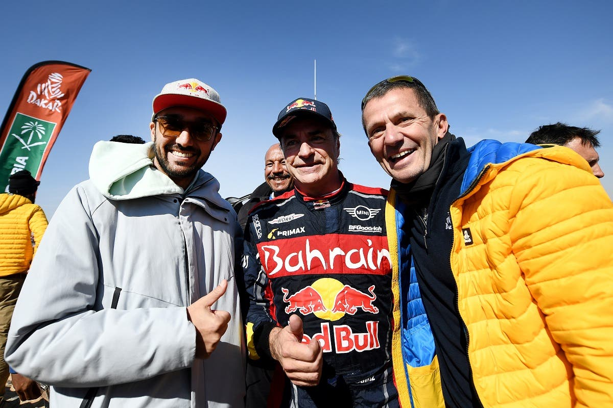 Saudi Arabia's Prince and head of General Sports autority Prince Abdulaziz bin Turki Al Saud (L), Spain's driver Carlos Sainz (C) and Managing director of Amaury Sport Organisation (ASO) Yann Le Moenner at the end of the stage 12 of the Dakar 2020 between Haradh and Qiddiya, in Qiddiya, Saudi Arabia, January 17, 2020. (AFP)