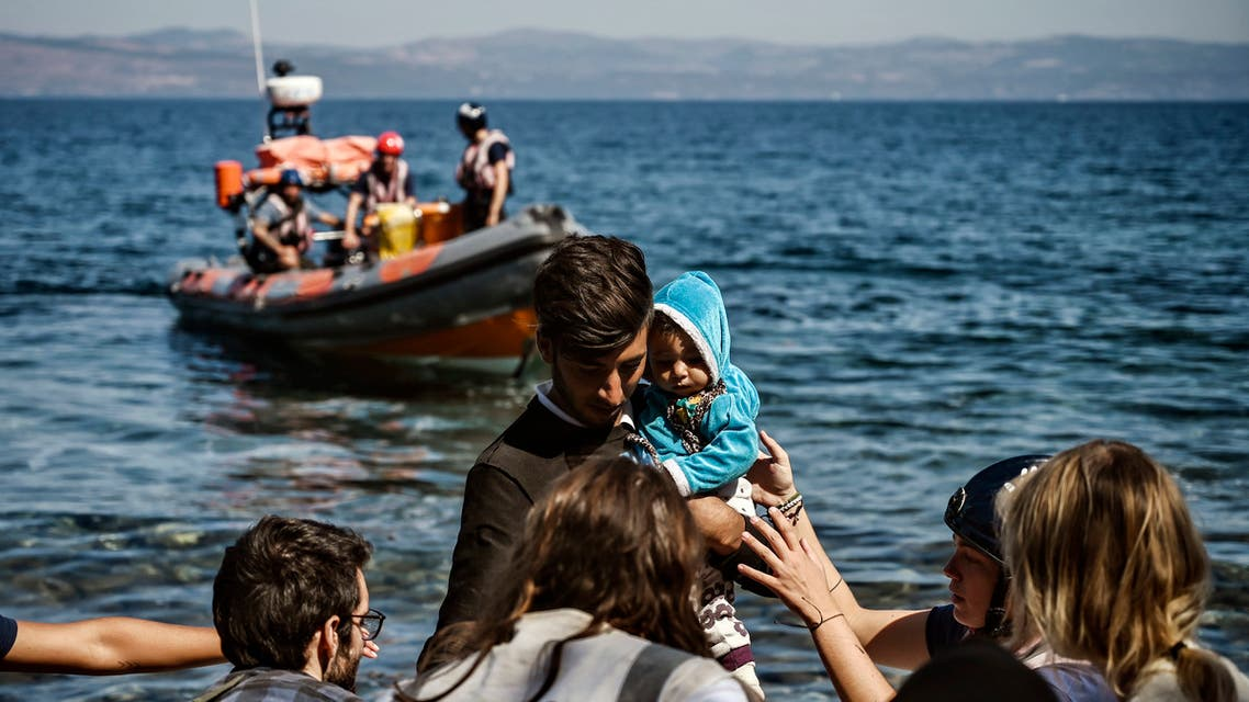 A migrant with a child is helped by rescuers as he arrives on the Greek island of Lesbos after crossing the Aegean Sea from Turkey, on September 16, 2019. Migration is a hot political issue in Europe, which experienced a wave of more than a million asylum-seekers in 2015, most of them from war-ravaged Syria.