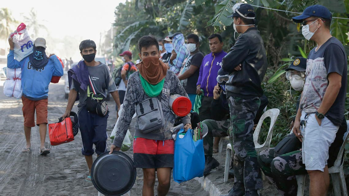 Men carry their belongings as authorities enforced total evacuation of residents living near the active Taal volcano in Agoncillo town. (AP)