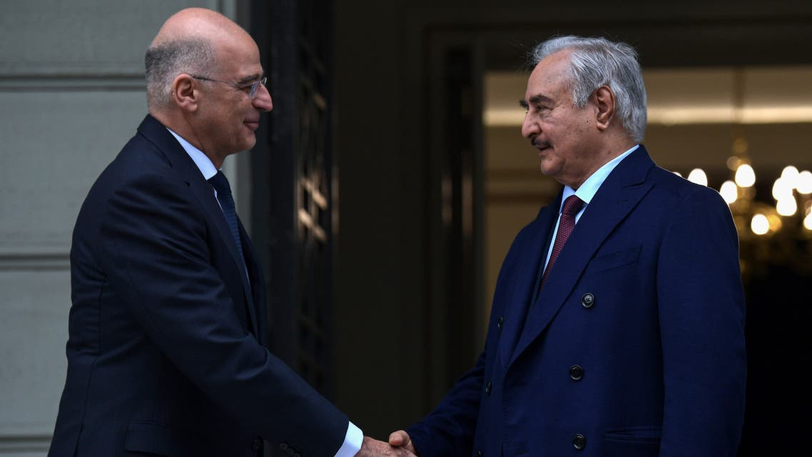 Greek Foreign Minister Nikos Dendias (L) welcomes Libyan strongman Khalifa Haftar before talks in Athens, on January 17, 2020, days ahead of a peace conference in Berlin which he and the head of Tripoli's UN-recognised government are expected to attend. The talks come as world powers step up efforts for a lasting ceasefire, nine months since an assault on Tripoli by Haftar's forces sparked fighting that has killed more than 280 civilians and 2,000 fighters, displacing tens of thousands.