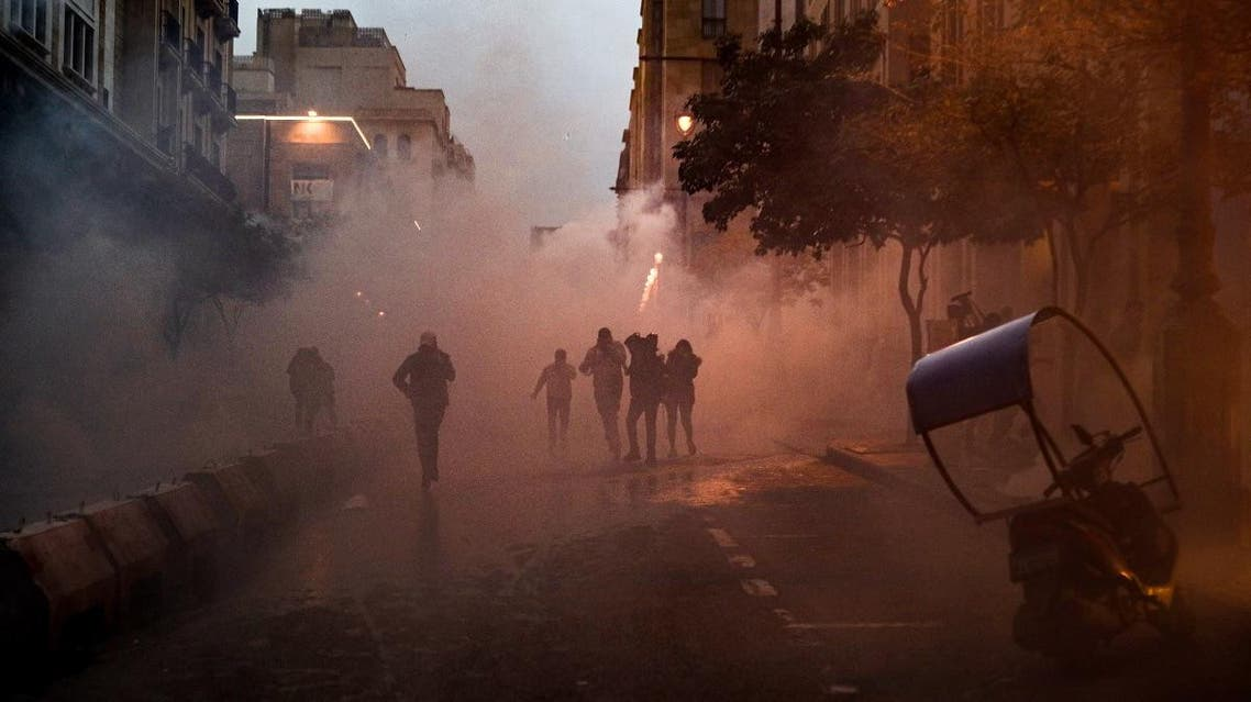 Anti-government protesters walk through clouds of tear gas during clashes with security forces in the central downtown district of the Lebanese capital near the parliament headquarters on January 18, 2020. (AFP)