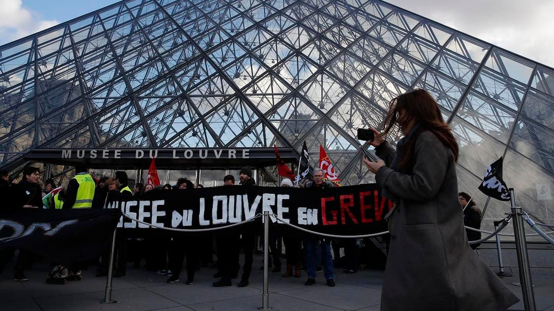 A visitor makes a video of striking employees demonstrating outside the Louvre museum Friday, Jan. 17, 2020 in Paris. (AP)