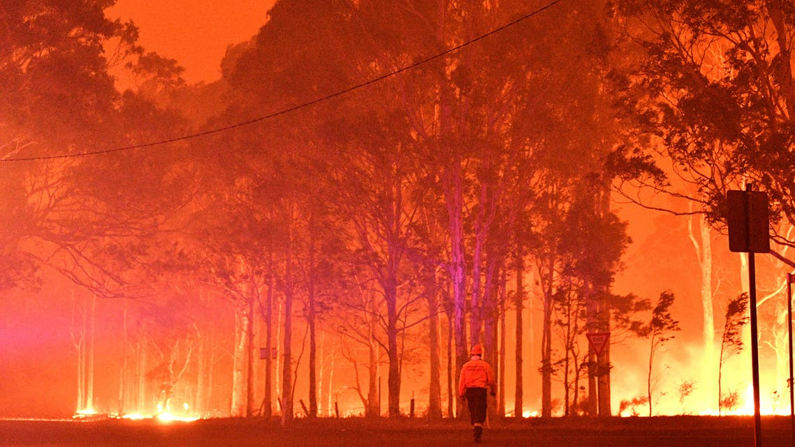 A firefighter walks past burning trees during a battle against bushfires around the town of Nowra in the Australian state of New South Wales on December 31, 2019. Thousands of holidaymakers and locals were forced to flee to beaches in fire-ravaged southeast Australia on December 31, as blazes ripped through popular tourist areas leaving no escape by land.