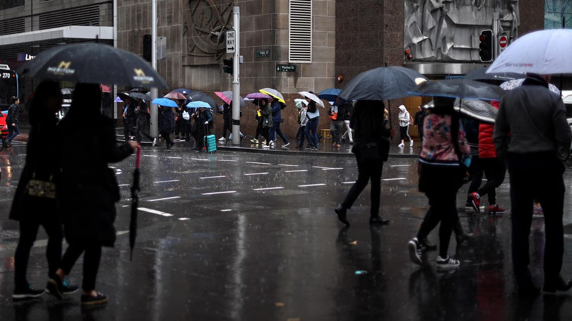 Office employees brace the rain during their lunch time break in the central business district of Sydney on September 17, 2019. (AFP)