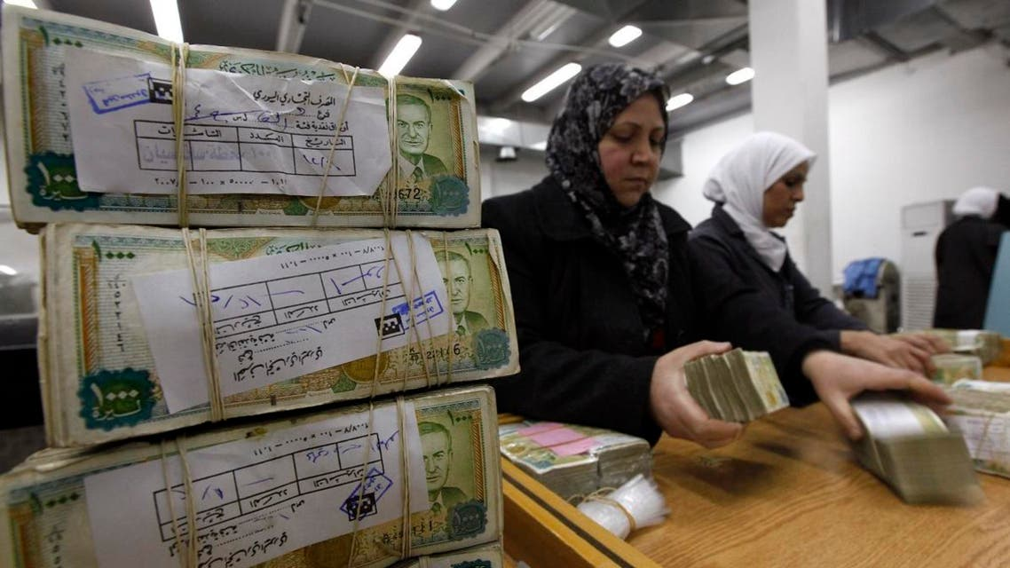 employees stack Syrian currency in the Central Bank, in Damascus, Syria.  (AP)