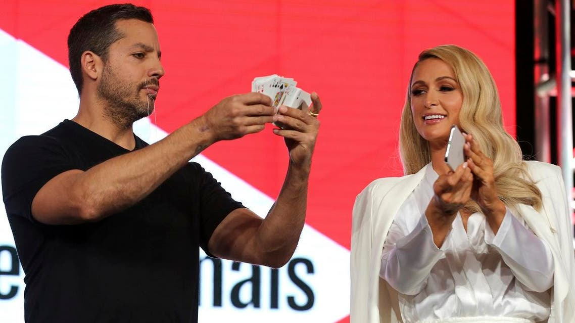 Illusionist David Blaine, left, performs live onstage as Paris Hilton assists him during the YouTube TCA 2020 Winter Press Tour at the Langham Huntington, on January. 18, 2020, in Pasadena, California. (AP)
