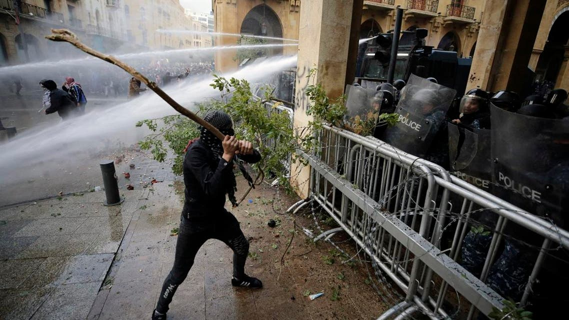 Anti-government demonstrators clash with riot police at a road leading to the parliament building in Beirut, Lebanon, Saturday, Jan. 18, 2020. (Photo: AP)