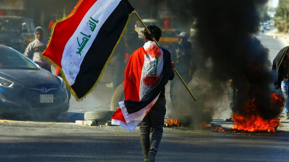 A demonstrator carries an Iraqi flag as he walks near burning tires, during ongoing anti-government protests in Najaf, Iraq January 12, 2020. (Photo: Reuters)