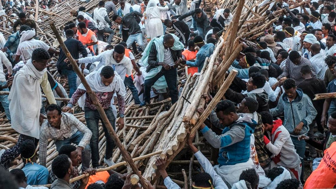 A crowd removes scaffoldings of a structure that collapsed, trapping and injuring dozens of people, during a religious celebration in Gondar, Ethiopia, on January 20, 2020. (AFP)