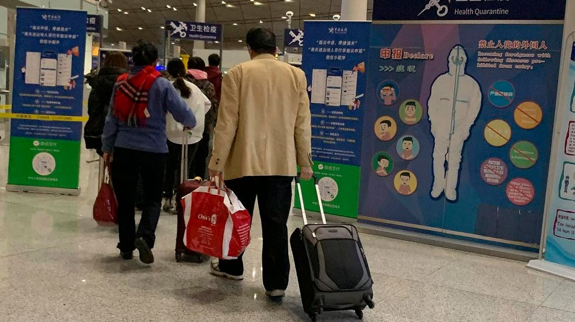 In this Jan. 13, 2020, photo, travelers pass by a health checkpoint before entering immigration at the international airport in Beijing. (AP)