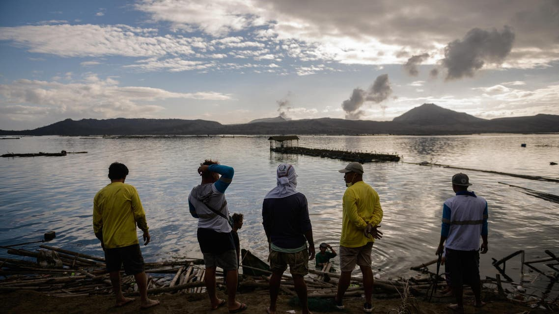 A group of fishermen make repairs to their operations affected by the ash-fall from the Taal volcano, January 20, 2020. (AFP)