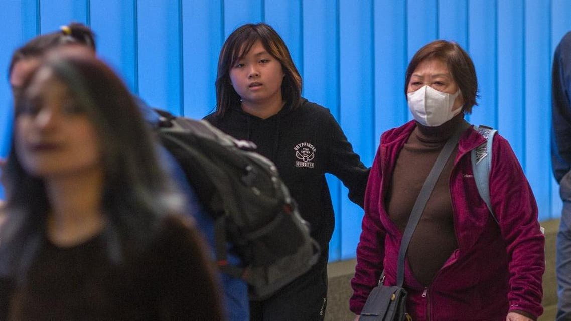 A woman arriving on a flight to Los Angeles International Airport wears a mask on the first day of health screenings for coronavirus of travelers from Wuhan, China. (AFP)