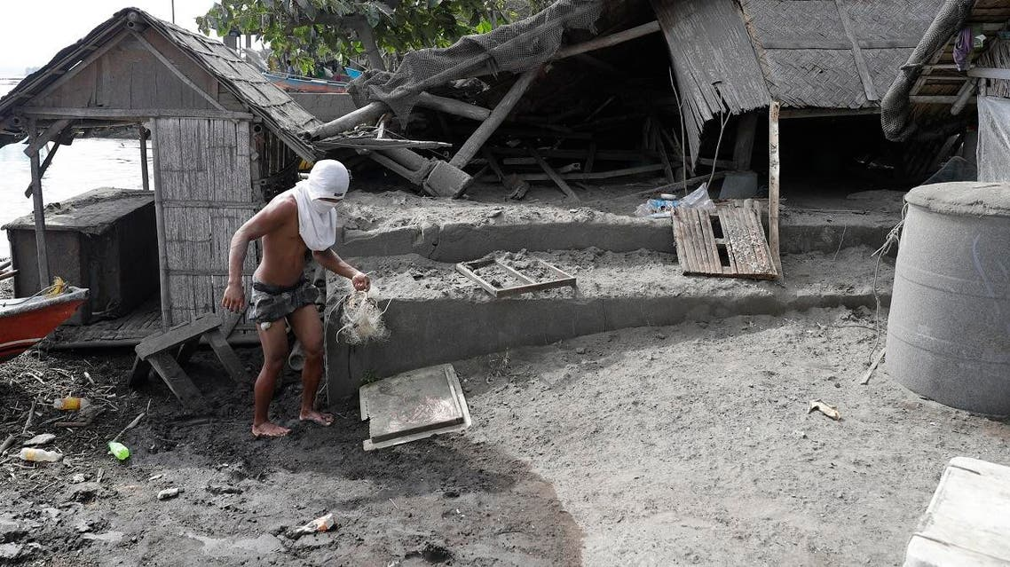 A fisherman stands beside a damaged house at a village near Taal volcano where residents have evacuated to safer grounds in Agoncillo, Batangas province. (AP)