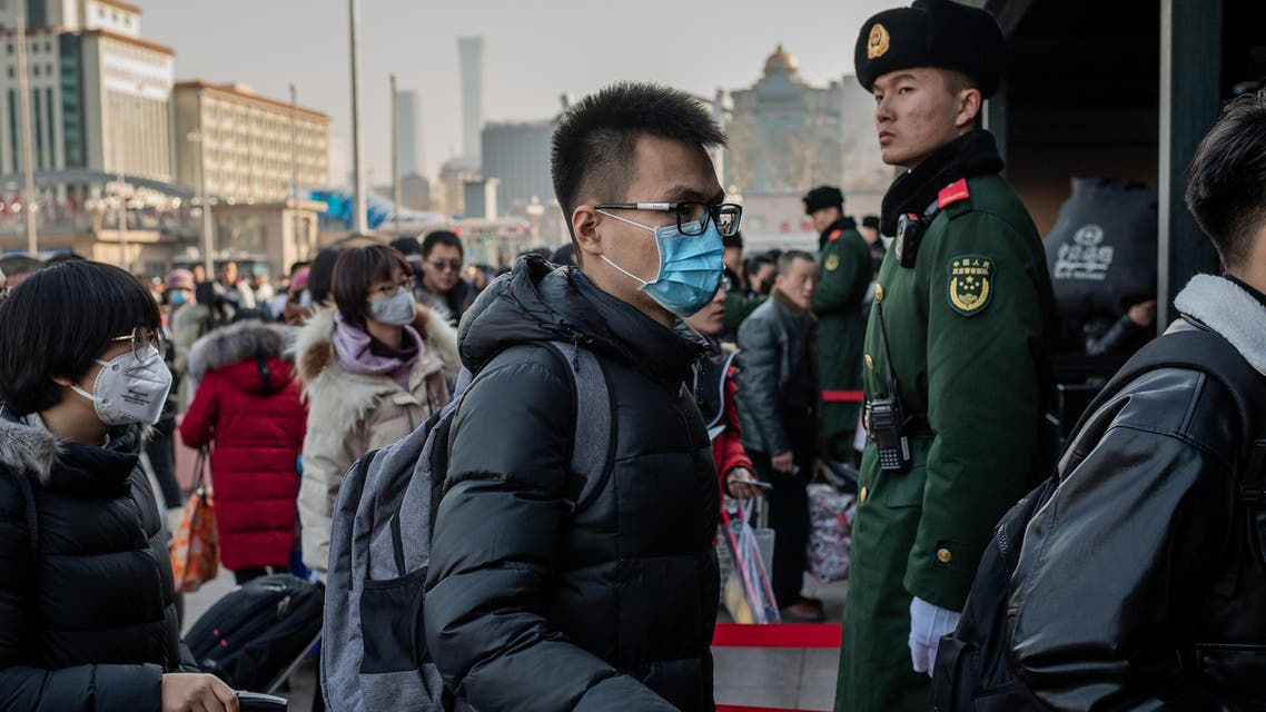 People wearing protective masks arrive at Beijing railway station to head home for the Lunar New Year on January 21, 2020. (AFP)