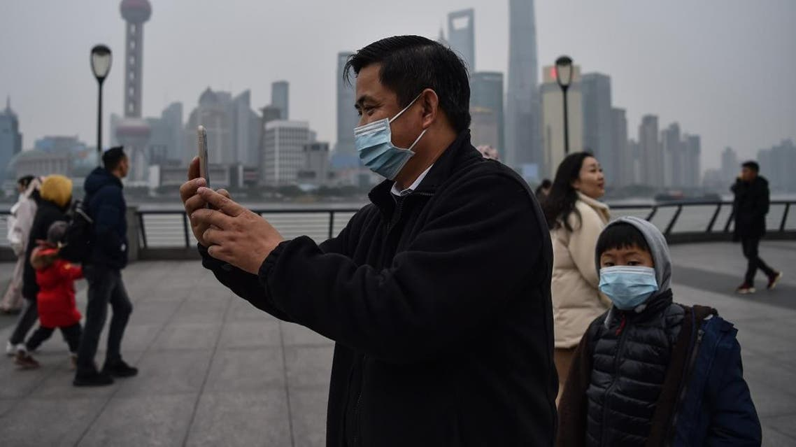 A man wearing a protective mask takes pictures on the promenade of the Bund along the Huangpu River in Shanghai on January 21, 2020. (Photo: Reuters)