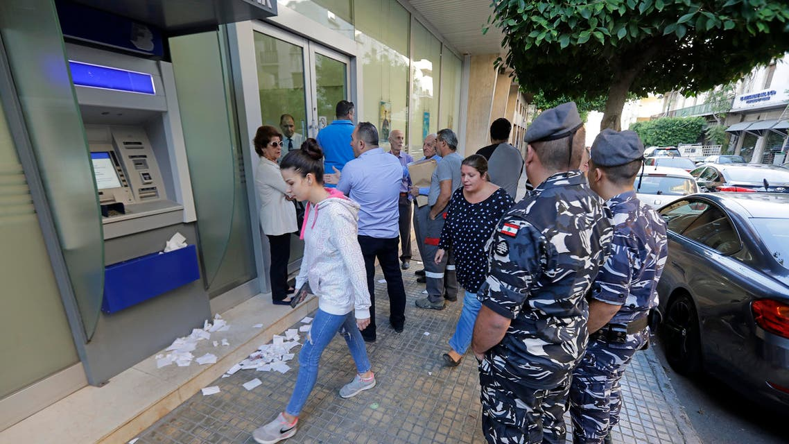 People await to enter a bank that has just reopened in the centre of the Lebanese capital Beirut. (AFP)