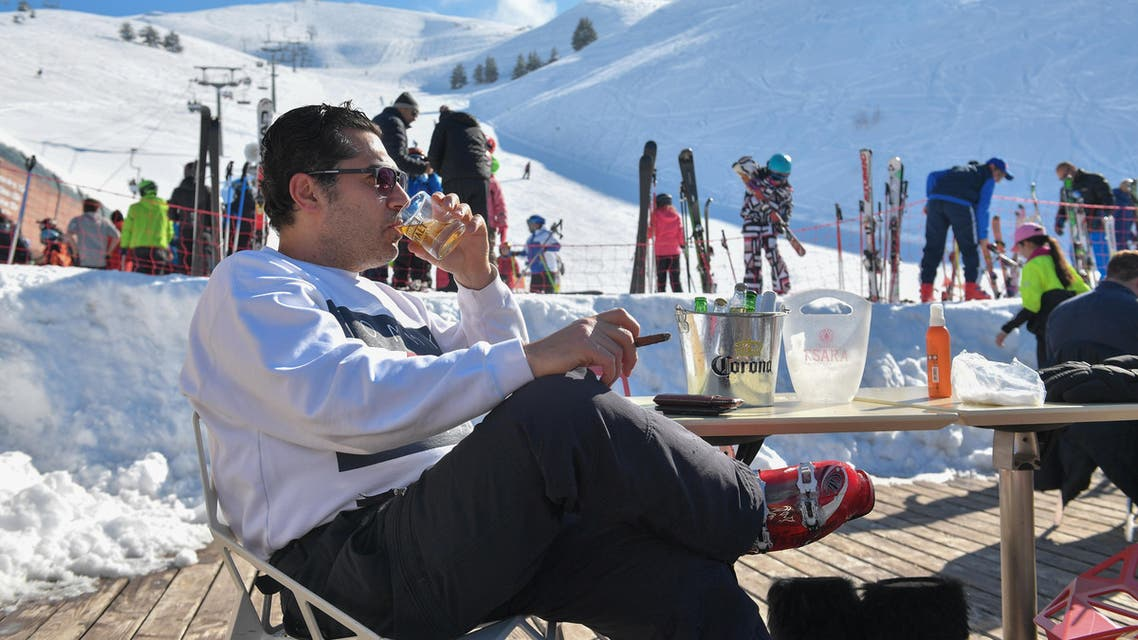A man sips whiskey and smokes a cigar at a ski resort in Lebanon. (Greg Demarque)