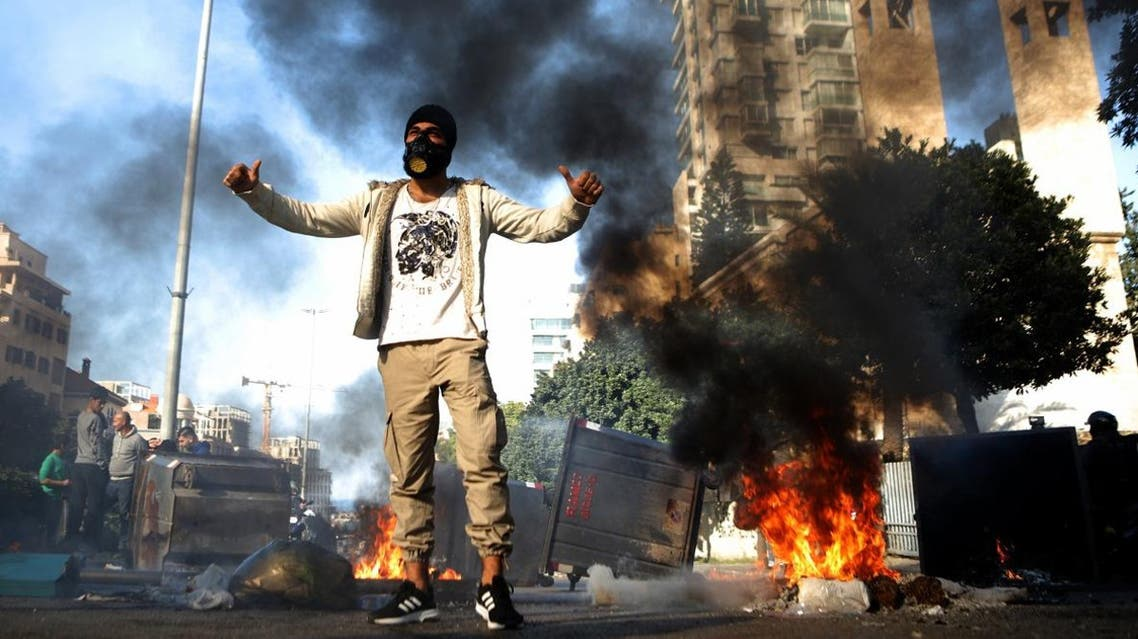 A Lebanese anti-government protester gestures next to burning garbage bins set up to block a road in the capital Beirut, on January 14, 2020. (Photo: AFP)