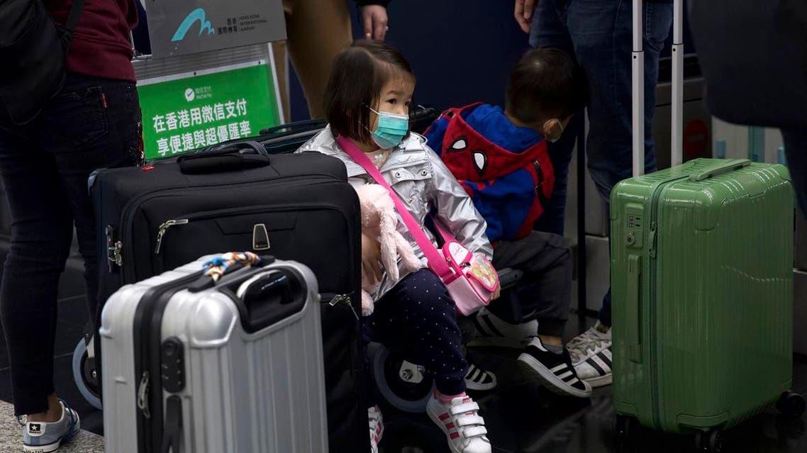 A girl wearing a face mask sits among suitcases at Hong Kong International Airport in Hong Kong, Tuesday, Jan. 21, 2020. (File photo: AP)