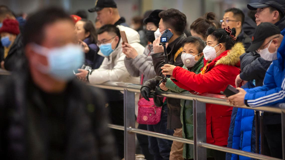 People wear face masks as they wait for arriving passengers at Beijing Capital International Airport on Jan. 23, 2020. (Photo: AP)
