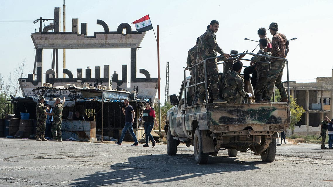 Members of the Syrian government forces sit atop a military vehicle in front of a welcome sign in the strategic town of Khan Sheikhun on August 24, 2019, after they announced the total control of the city a day before. Regime forces massed today in northwest Syria, a monitor said, in an apparent bid to press an offensive against jihadists and allied rebels that has heightened tensions with neighbouring Turkey.