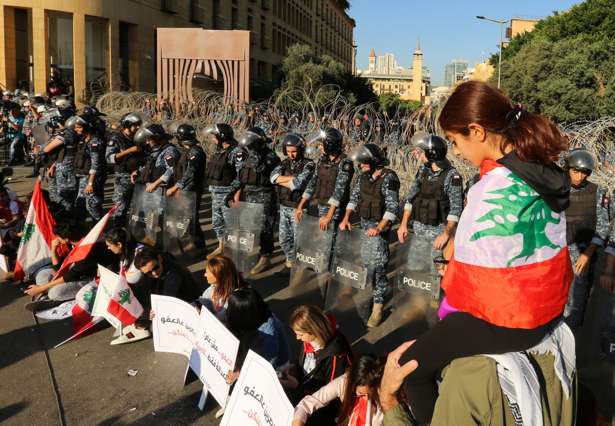 A girl has the national flag draped over her shoulders as riot police stand guard, during the ongoing anti-government protest, in Beirut, Lebanon, November 19, 2019. (Reuters)