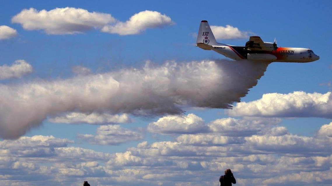 Photographers take photographs of the Large Air Tanker (LAT) C-130 Hercules, also known as 'Thor', as it drops a load of around 15,000 liters during a display by the Rural Fire Service ahead of the bushfire season at RAAF Base Richmond Sydney, Australia, September 1, 2017. (File photo: Reuters)