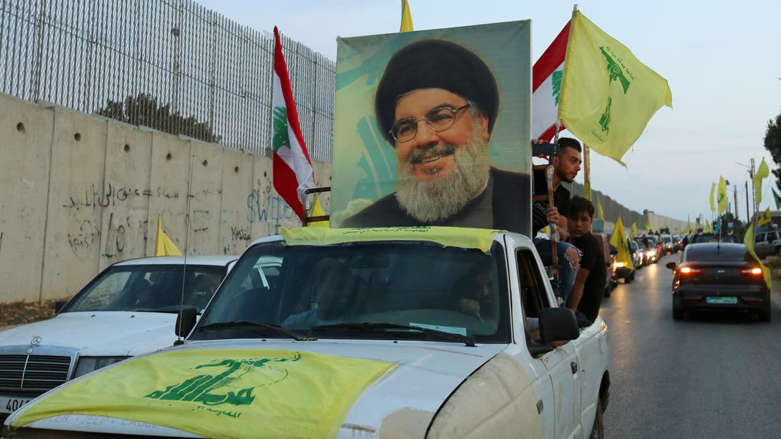 Supporters of Lebanon's Hezbollah leader Sayyed Hassan Nasrallah ride in a vehicle decorated with Hezbollah and Lebanese flags and a picture of him, as part of a convoy in Lebanon. (Reuters)